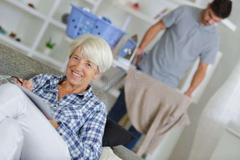 Manlig kvinna för åldring för anhörigvårdarestrykningtvätteri royaltyfri fotografi