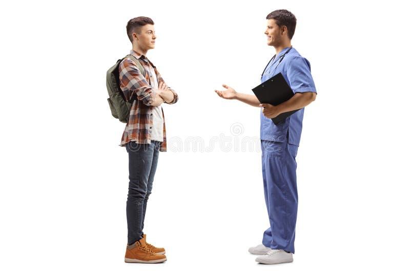 Manlig läkare i en blå uniform som talar med en manlig student arkivbilder