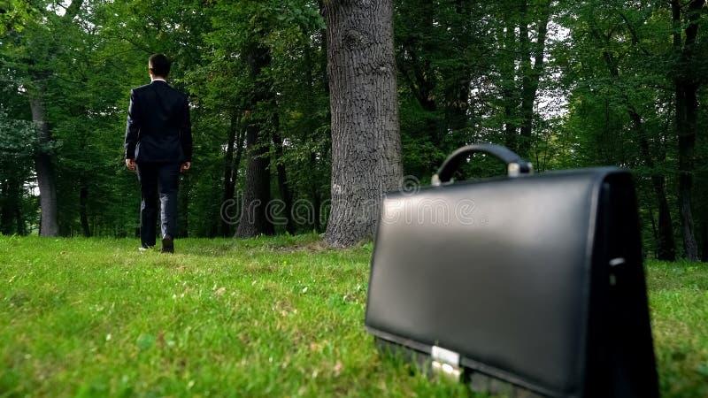 Manlig lämna portfölj på gräs och gå i skogen, upptagen livsstil för flykt royaltyfri fotografi