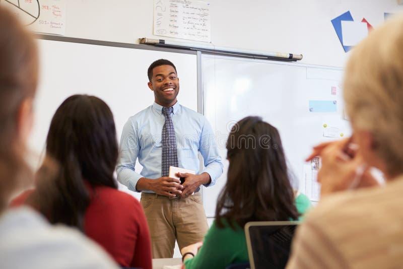 Manlig lärare framme av studenter på en vuxenutbildninggrupp royaltyfri bild