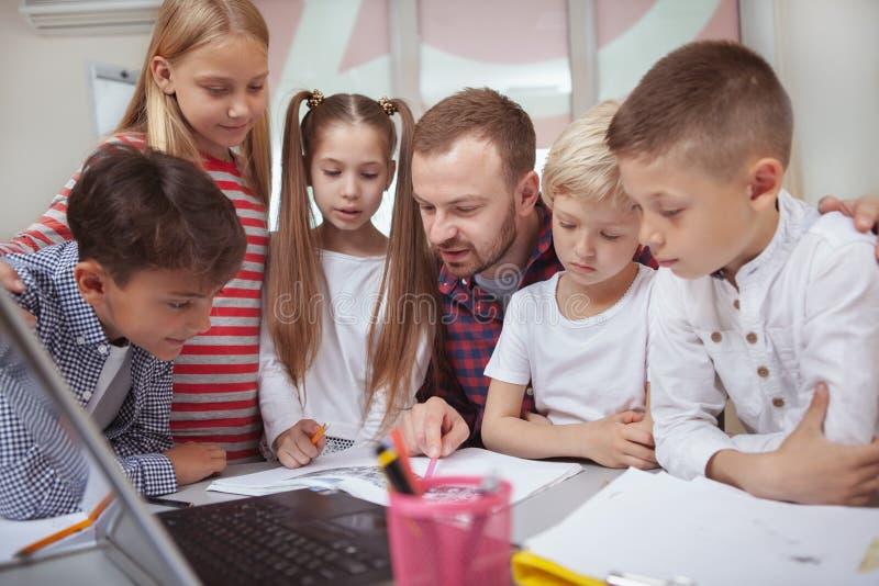Manlig lärare som arbetar med barn på förträningen arkivbild