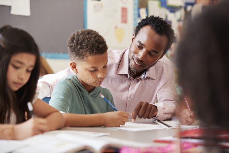 Manlig lärare som arbetar med grundskolapojken på hans skrivbord royaltyfria foton