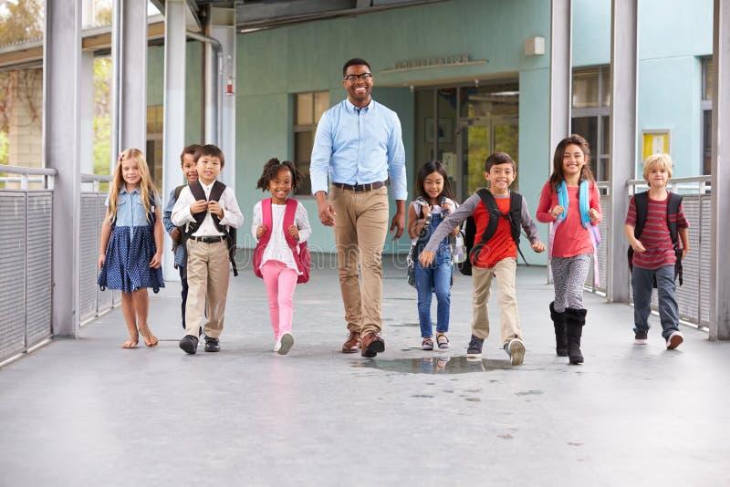 Manlig lärare som går i korridor med grundskolaungar royaltyfria foton