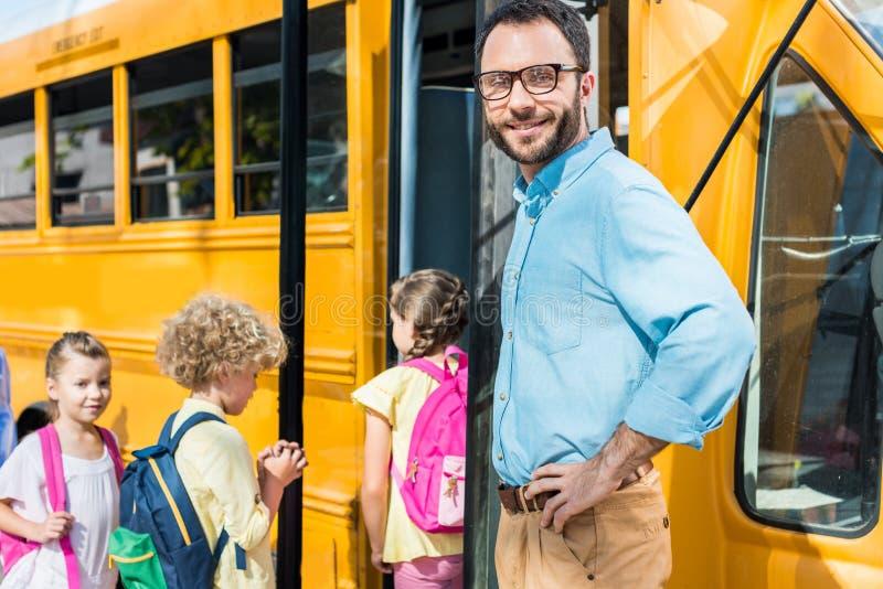 manlig lärare som ser kameran medan elever som skriver in den gjorda suddig skolbussen royaltyfria foton