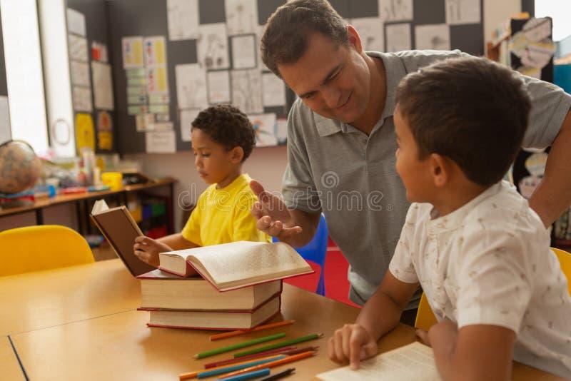 Manlig lärare som undervisar en skolpojke i ett klassrum arkivfoto