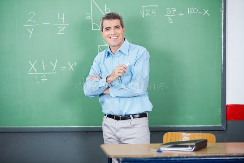 Manlig lärare Standing Arms Crossed mot bräde arkivbild
