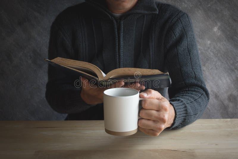 Manlig läsning för papper för kopp för svart kaffe på en trätabell arkivbilder