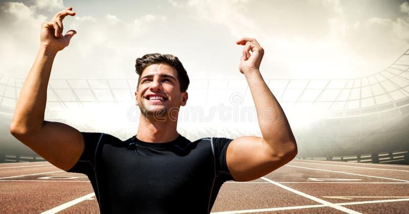 Manlig löpare med händer i luft på spår mot signalljus fotografering för bildbyråer