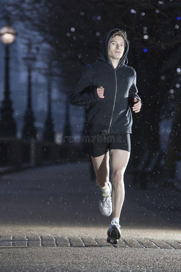 Manlig löpare på tidig vintermorgon arkivfoton