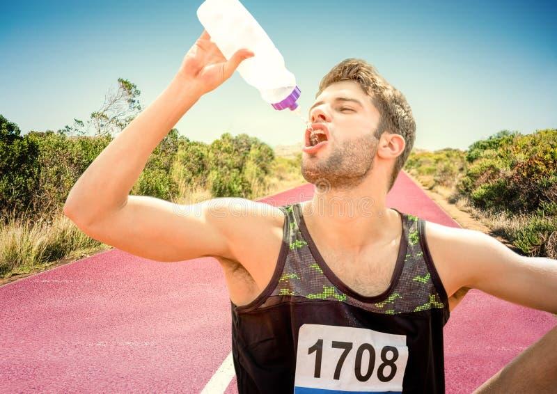 Manlig löpare som dricker på spår i öken arkivfoton