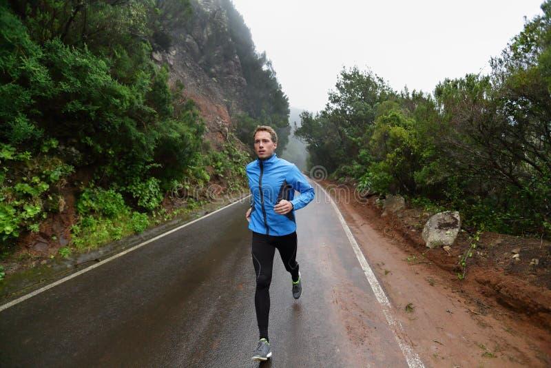 Manlig löpare som joggar och kör på vägen i natur arkivbilder
