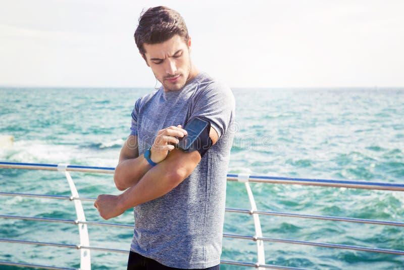 Manlig löpare som justerar inställningar på armbindeln för smartphone royaltyfria foton