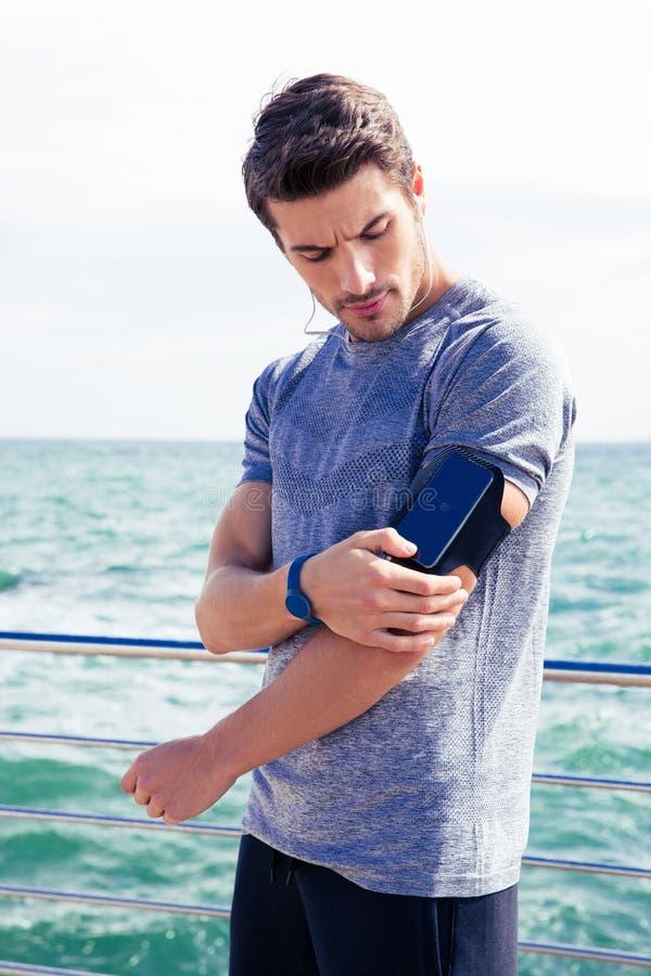 Manlig löpare som lyssnar till musik som justerar inställningar på armbindeln för smartphone arkivbilder