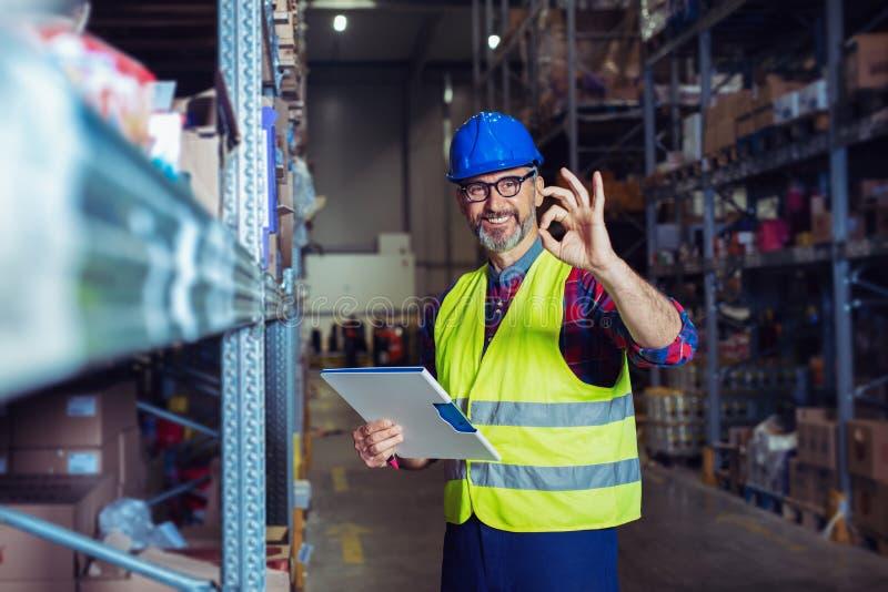 Manlig lagerarbetare med skrivplattan arkivbild