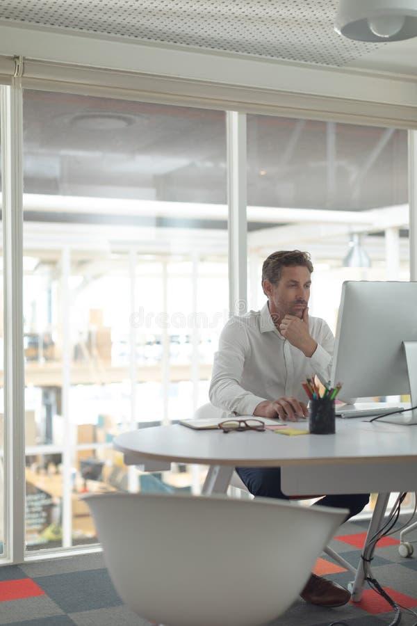 Manlig ledare för affär som arbetar på datoren på skrivbordet i ett modernt kontor royaltyfria foton