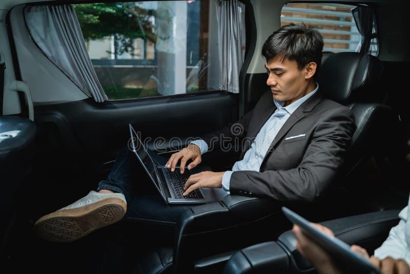 Manlig ledare som använder bärbara datorn, medan passera bilen arkivfoto