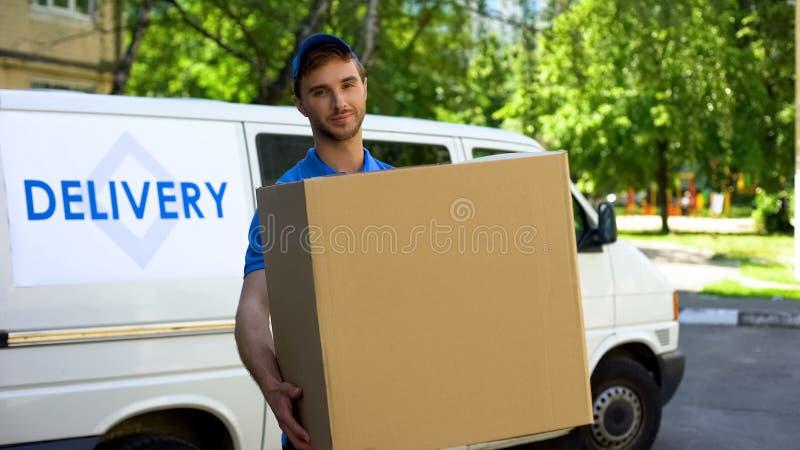 Manlig leveransarbetare som rymmer den stora asken, snabb packeleverans till hemmet, service royaltyfri fotografi