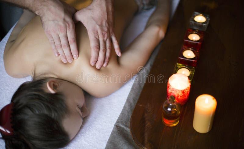 Manlig manuell arbetare som gör brunnsortmassage av skuldror och halsen till unga flickan i mörkt rum royaltyfria bilder