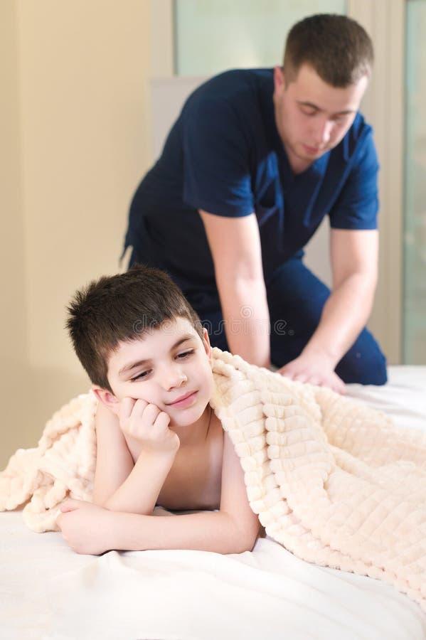 Manlig manuell terapeut som masserar kalvar av en liten patient Liten eftertänksam pojke på mottagandet av tillvägagångssättet av fotografering för bildbyråer