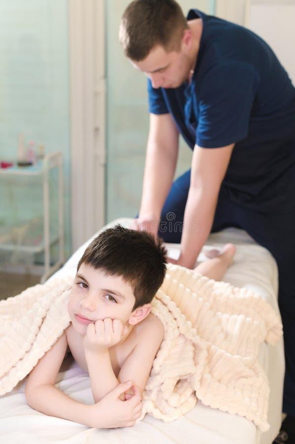 Manlig manuell terapeut som masserar kalvar av en liten patient Liten eftertänksam pojke på mottagandet av tillvägagångssättet av arkivfoton