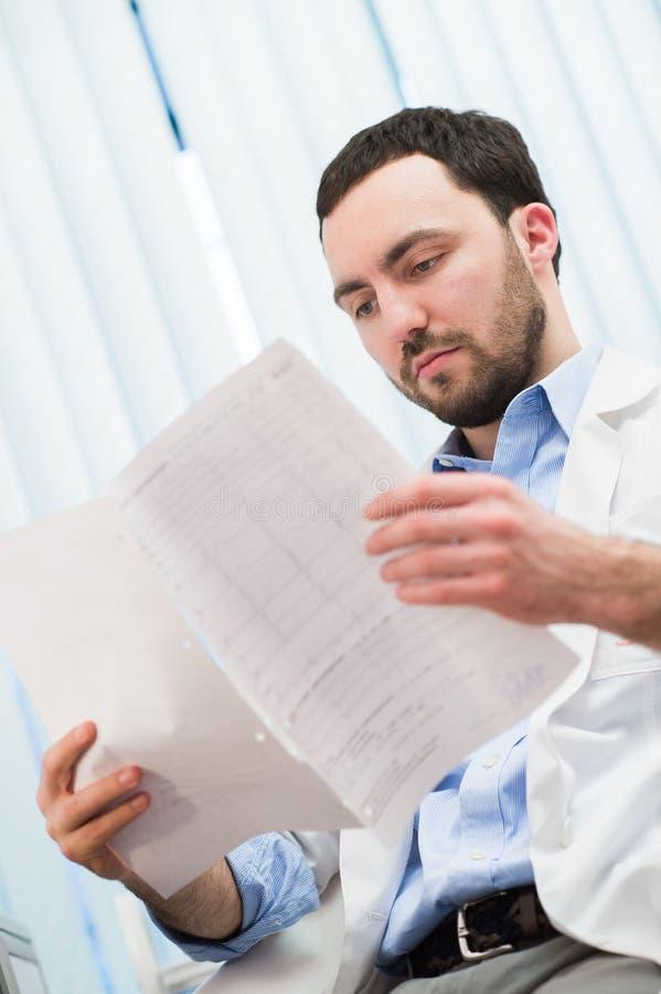 Manlig medicindoktor som kontrollerar något på hans legitimationshandlingar Medicinsk vård, försäkring, recept, skrivbordsarbete  royaltyfri foto