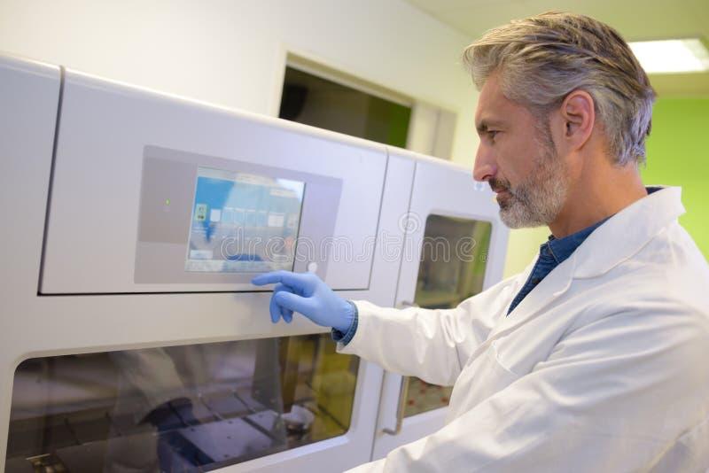 Manlig medicinsk tekniker som programmerar maskinen royaltyfria bilder