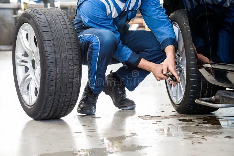 Manlig mekaniker Changing Car Tire i garage royaltyfria foton