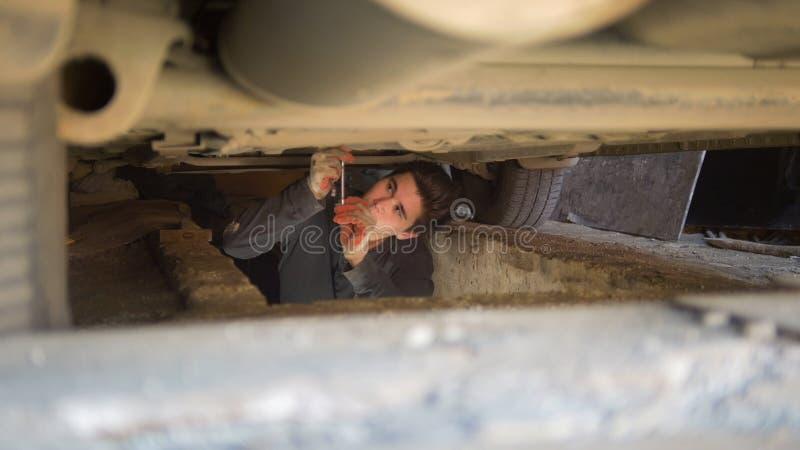Manlig mekaniker under en bil som når för en skruvmejsel i garage arkivfoto