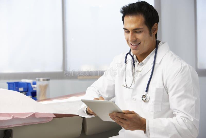 Manlig minnestavla för doktor In Surgery Using Digital arkivbild