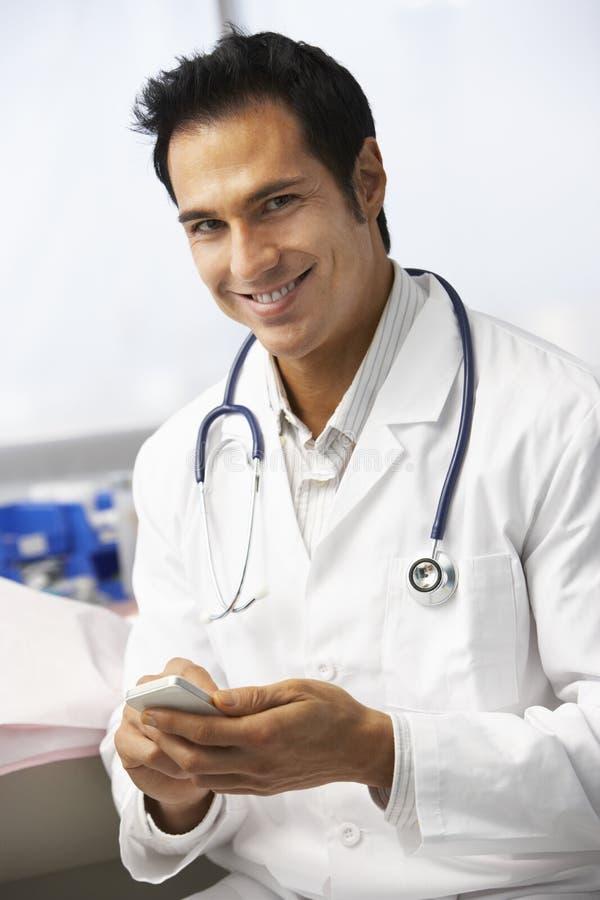 Manlig mobiltelefon för doktor In Surgery Using arkivfoton