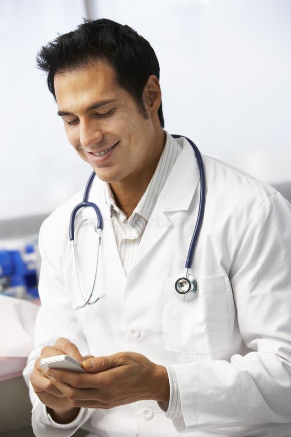 Manlig mobiltelefon för doktor In Surgery Using royaltyfri bild