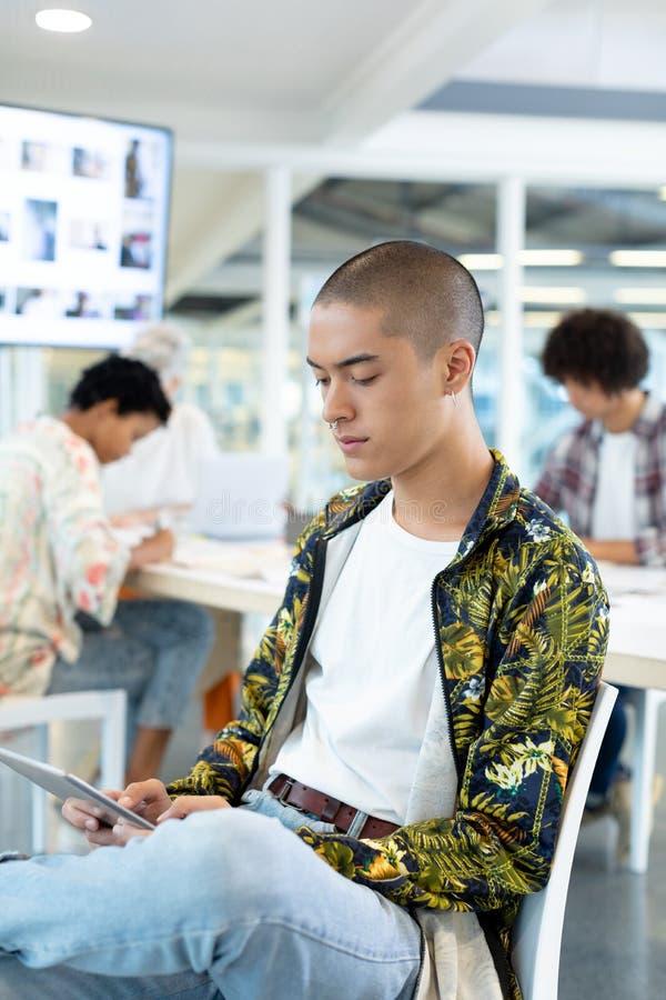 Manlig modeformgivare som använder den digitala minnestavlan i konferensrummet royaltyfri foto