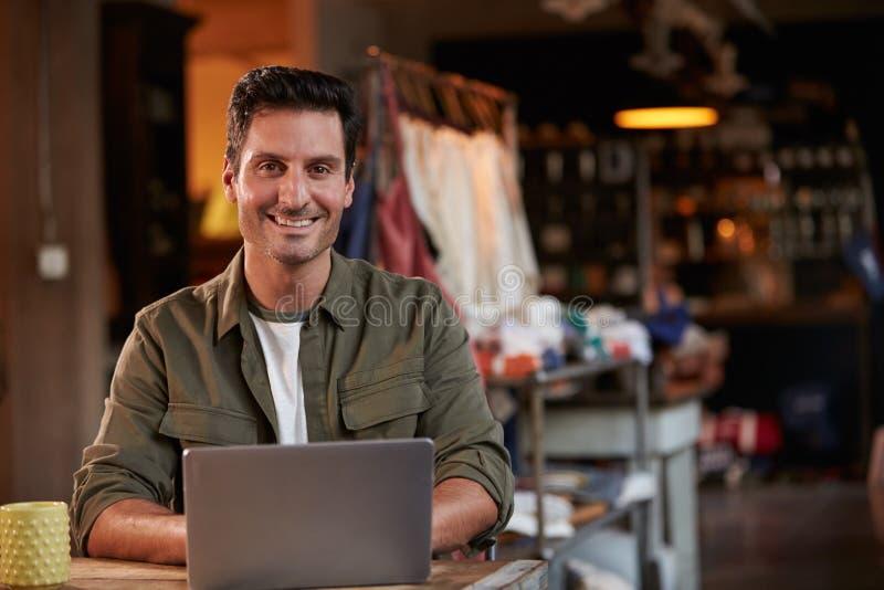 Manlig modeformgivare Working At Laptop i studio arkivbild