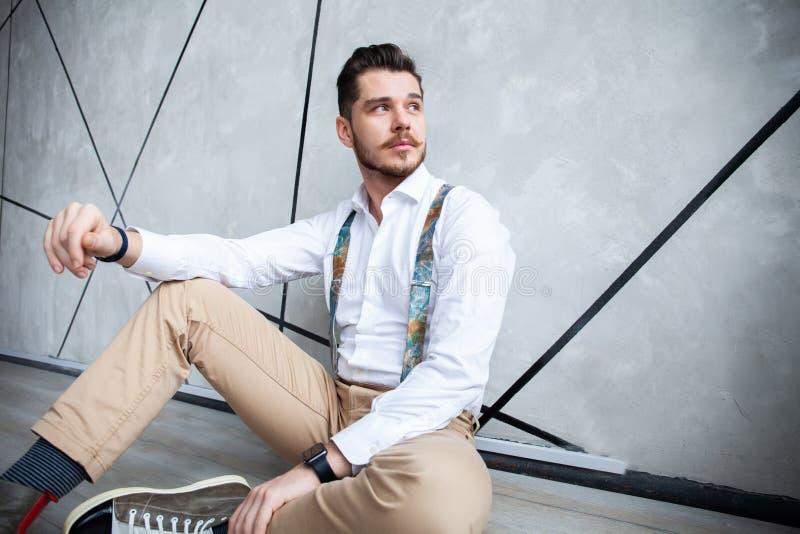 Manlig modell för kallt mode som sitter på grå bakgrund och ser kameran royaltyfria foton