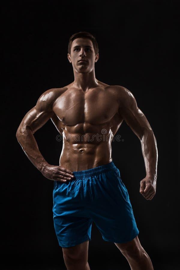 Manlig modell för muskulös och färdig ung kroppsbyggarekondition som poserar över svart bakgrund arkivfoton