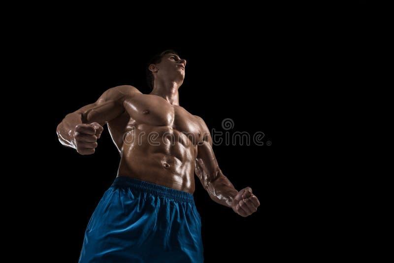 Manlig modell för muskulös och färdig ung kroppsbyggarekondition som poserar över svart bakgrund arkivbild