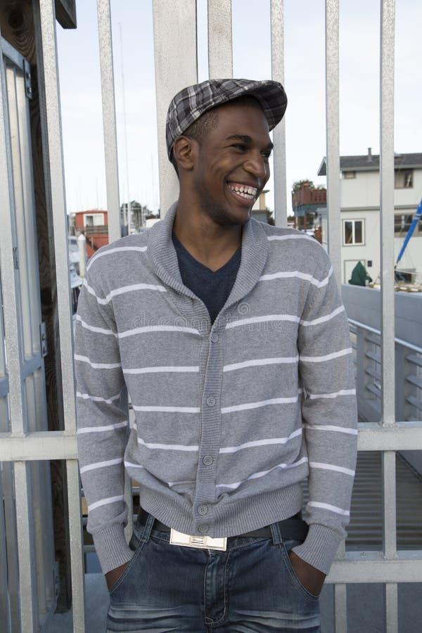 Manlig modell för stilig afrikansk amerikan som skrattar den utomhus- ståenden arkivbild