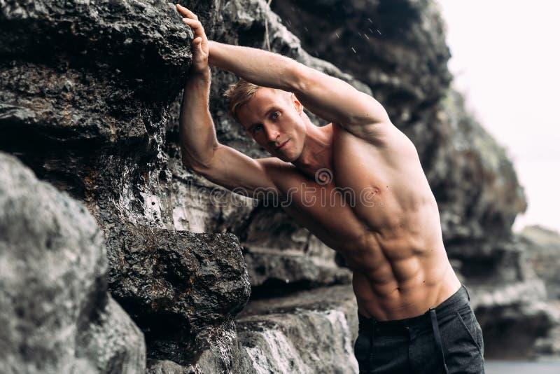 Manlig modell f?r sexig kondition i svarta fl?sanden och shirtless posera p? den svarta sandiga stranden fotografering för bildbyråer