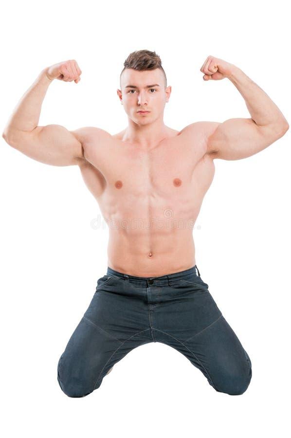 Manlig modell på hans knä som böjer starka armar royaltyfria foton