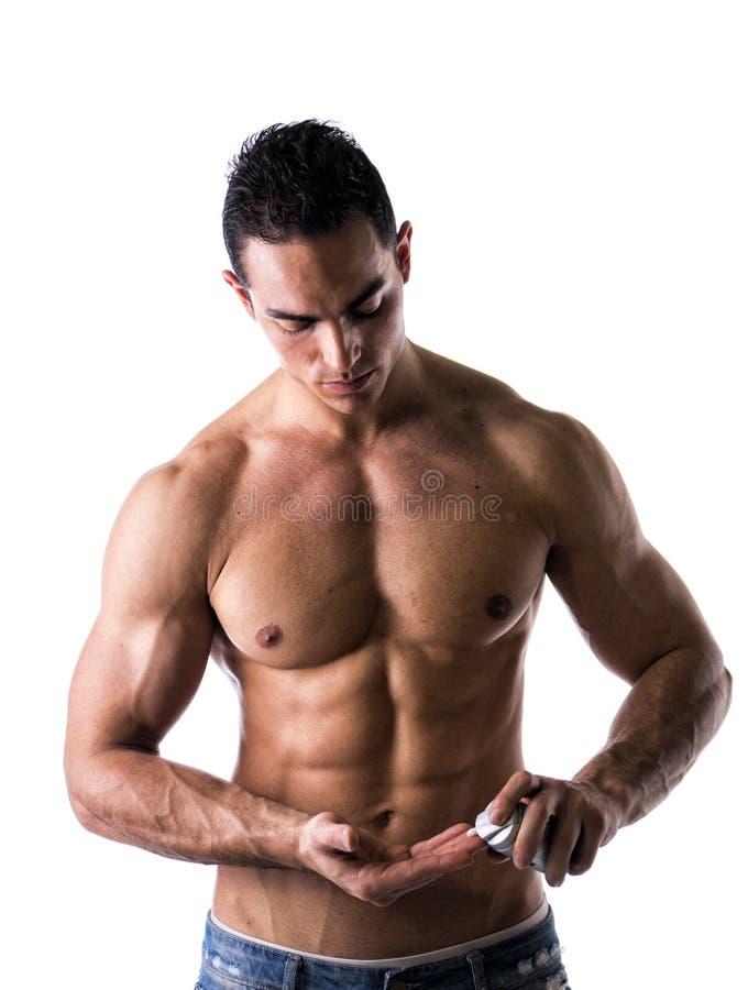 Manlig modell som sätter kräm i hans hand arkivfoton