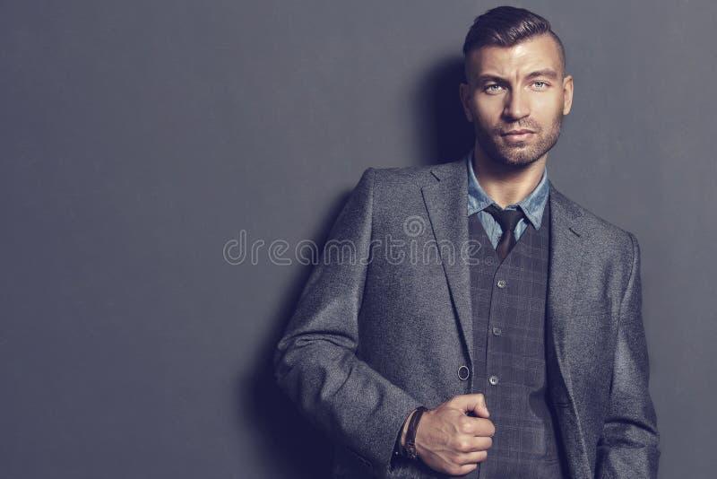 Manlig modemodell i elegant dräkt på grå väggbakgrund Stilig man i trendig kläder Stående av affärsmannen arkivfoton