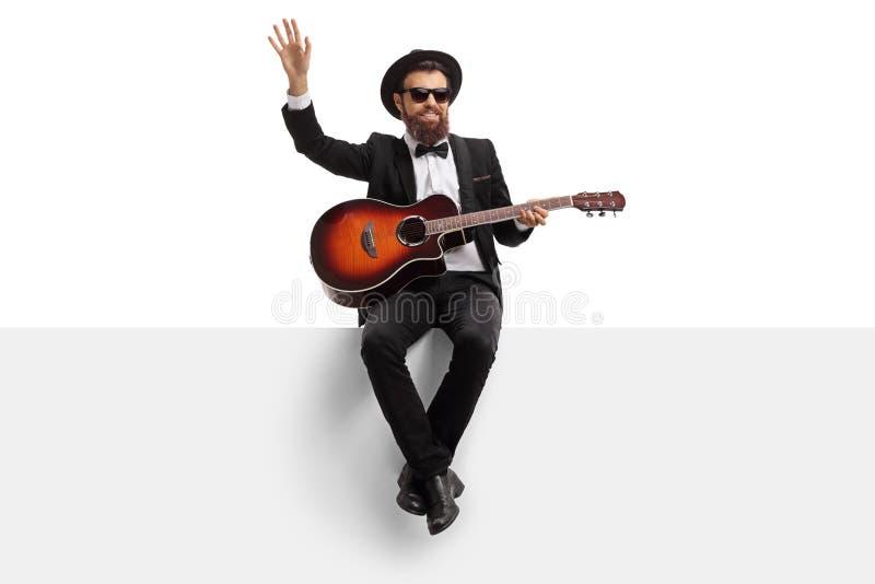 Manlig musiker med en akustisk gitarr som sitter på ett vitt baner och vinka royaltyfri bild