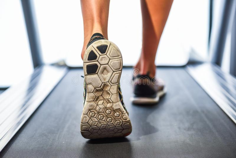 Manlig muskulös fot i gymnastikskor som kör på trampkvarnen på Get royaltyfri foto
