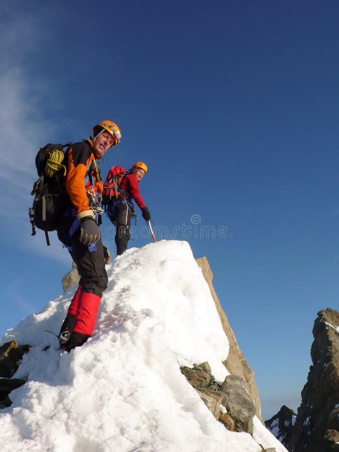 Manlig och kvinnlig bergsbestigare på en utsatt stenig toppmötekant på deras väg till ett högt alpint bergmaximum fotografering för bildbyråer