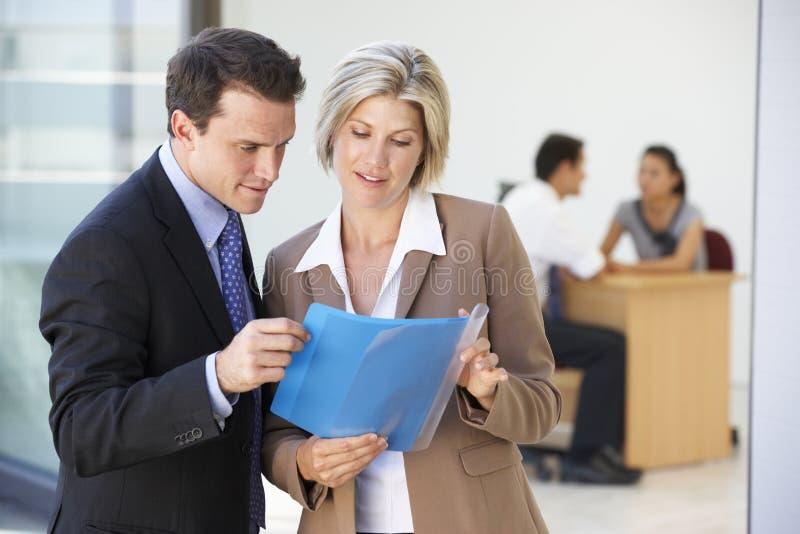 Manlig och kvinnlig utövande diskuterande rapport med kontorsmöte i bakgrund royaltyfri foto