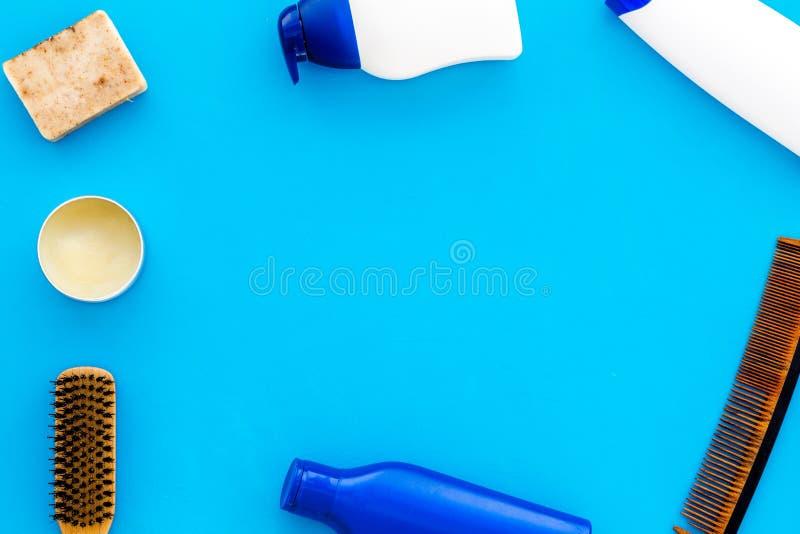Manlig omsorguppsättning för frisersalong med schampoflaskan och hårkammen på ljust - blå modell för bästa sikt för bakgrund royaltyfri fotografi