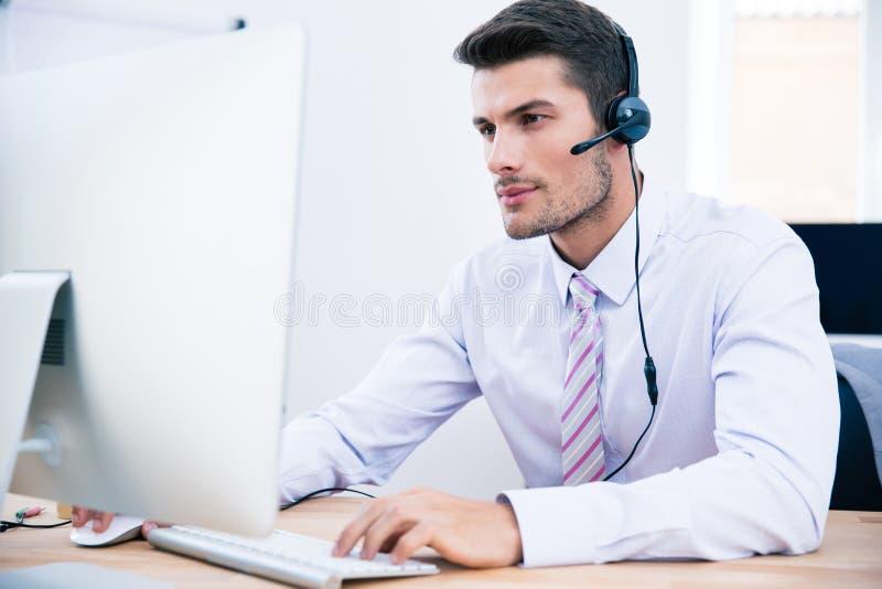Manlig operatör som i regeringsställning arbetar på PC royaltyfri foto