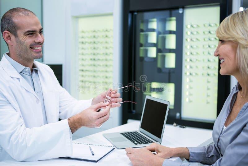 Manlig optometriker som talar till den kvinnliga patienten arkivbilder