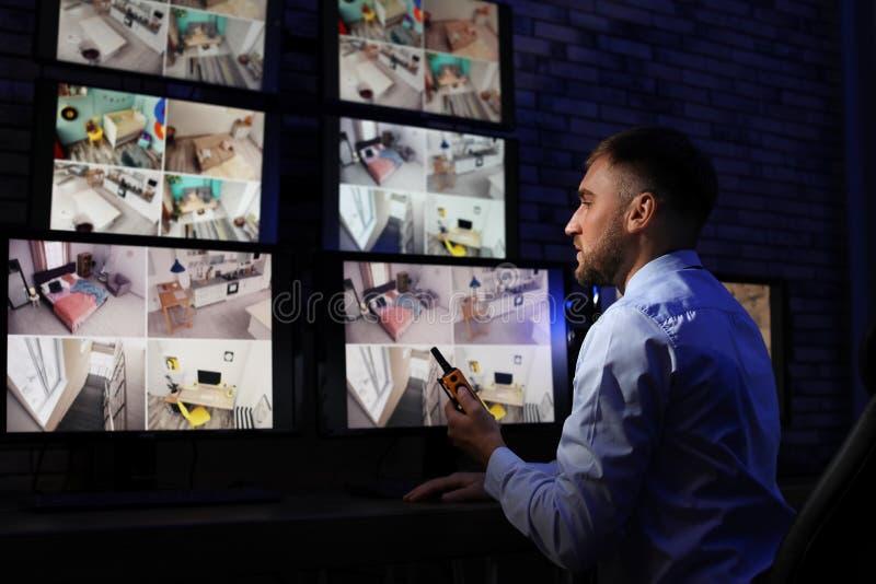 Manlig ordningsvakt med den bärbara sändaren som inomhus övervakar hem- kameror arkivbilder