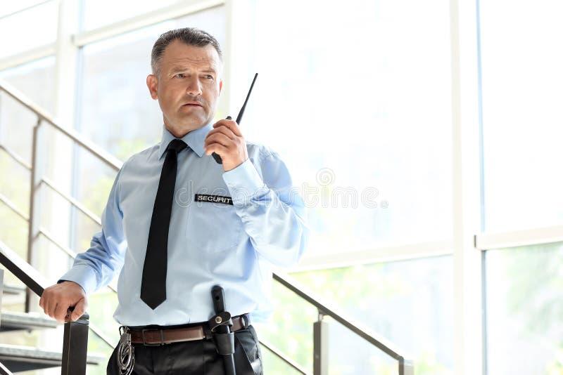 Manlig ordningsvakt som använder sändaren för bärbar radio arkivbild